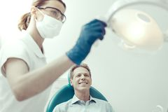 Happy patient sitting in a dental chair and smiling stock images