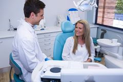 Happy patient talking with dentist Stock Photo