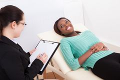 Happy patient talking to psychologist Stock Photography