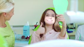 Woman checking their teeth at mirror after dental treatment in dentist office