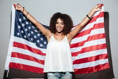Happy patriotic african woman holding US flag stock photo