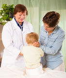 Happy   pediatrician doctor examining toddler Royalty Free Stock Image