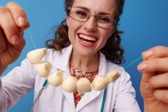 Happy pediatrist doctor on blue putting on garlic beads Royalty Free Stock Image