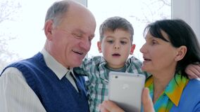 Happy pensioner family uses mobile phone to communicate on Internet in room. Close-up stock video footage
