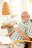 Happy pensioner reading at home. Sitting in armchair, smiling at camera Royalty Free Stock Photos