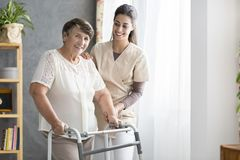 Pensioner and nurse. Happy pensioner trying to walk in a senior home with support of the nurse stock images