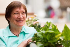 Happy pensioner woman relaxed on balcony Stock Images