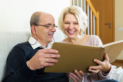 Happy pensioners watching old photoes Royalty Free Stock Image