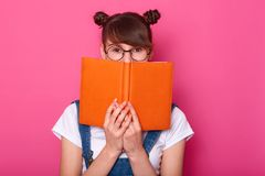 Happy pensive girl standing isolated over pink background in studio, holding orange notebook, covering half of face, looking. Attentively at camera, having stock photography
