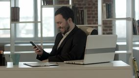 Happy people with businessman on the phone typing text message in office. Professional shot in 4K resolution. You can use it e.g. in your commercial video Royalty Free Stock Photo
