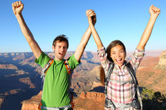 Happy people celebrating cheering in Grand Canyon. Young multiethnic couple on hiking travel excited and elated in Grand Canyon, south rim, Arizona, USA. Asian Stock Photography