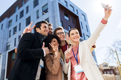 Happy people with conference badges taking selfie Royalty Free Stock Photography