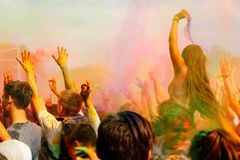 Happy people crowd partying under colorful powder cloud at holi royalty free stock photos