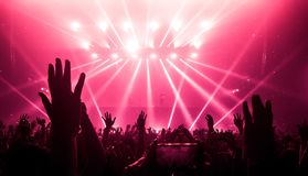 Happy people dance in nightclub party concert. And listen to music from DJ on the stage in background. Cheerful crowd celebrate Christmas and New Year party Royalty Free Stock Photo