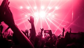 Happy People Dance in Nightclub Party Concert. And listen to music from DJ on the stage in background. Cheerful crowd celebrate Christmas and New Year party royalty free stock image