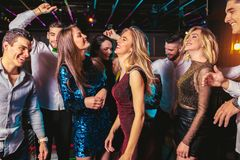 Happy people are dancing in club. Nightlife and disco concept royalty free stock photos