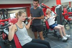 Happy people doing indoor biking in fitness club Stock Images