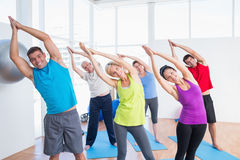 Happy people doing stretching exercise in yoga class