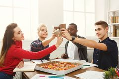 Students learning and eating pizza. Happy people eating pizza and cheering with paper cups at coworking office during break. Food delivery and team work concept Royalty Free Stock Photography