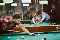 Happy people enjoying playing pool together royalty free stock images