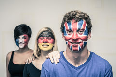 Happy people with European flags on faces. Group of happy people with painted European flags on their faces royalty free stock photos