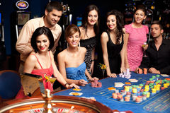 Happy people excited about roulette bet outcome Stock Photos
