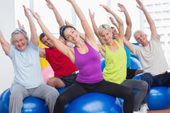 Happy people exercising in gym class. Portrait of happy men and women on fitness balls exercising in gym class Stock Image