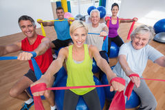 Happy people exercising with resistance bands in gym class. Portrait of happy men and women on fitness balls exercising with resistance bands in gym class Stock Photo