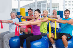 Happy people exercising with resistance bands in gym. Portrait of happy men and women on fitness balls exercising with resistance bands in gym Royalty Free Stock Photography