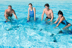 Happy people exercising with water aqua bike Stock Images