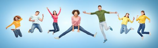 Happy people or friends jumping in air over blue Royalty Free Stock Photos