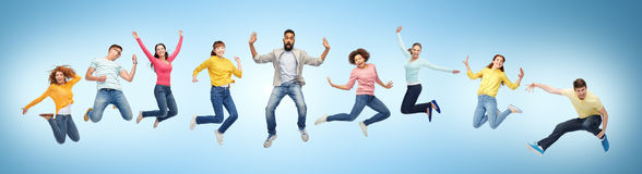 Happy people or friends jumping in air over blue royalty free stock photo