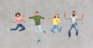 Happy people or friends jumping in air over gray stock photography