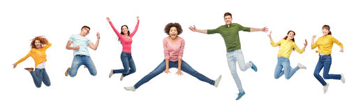 Happy people or friends jumping in air over white. Happiness, freedom, motion and people concept - smiling young international friends jumping in air over white Royalty Free Stock Photos