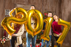 Happy people with golden balloons. Group of happy people with golden 2017 sign balloons Royalty Free Stock Image