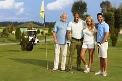 Happy people on golf course. Happy people smiling, hugging on the golf course, ready to play, looking at camera stock photo