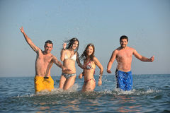 Happy people group have fun and running on beach Stock Images