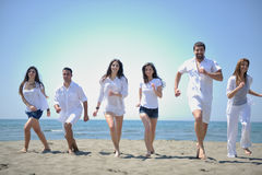 Happy people group have fun and running on beach Stock Photography