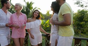 Happy People Group Talking Outdoors On Terrace Looking At Beautiful Landscape With Sunset Over Tropical Forest, Friends. Gathering Together Slow Motion 60 stock video footage