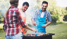 Happy people having camping and having bbq party. Outdoor stock image