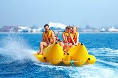 Happy people having fun on banana boat royalty free stock photography
