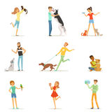 Happy people having fun with pets, man and women training and playing with their pets  Royalty Free Stock Photos