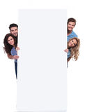 Happy people hiding behing a big blank billboard. Four casual happy people hiding behing a big blank billboard on white background royalty free stock photo