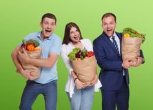 Happy people hold bags with healthy food, grocery buyers isolated Royalty Free Stock Images