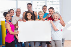 Happy people holding blank billboard at health club Stock Photo