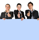 Happy people holding a board and give thumbs-up. Group of three business people holding a blue blank board and giving thumbs -up concept of successful lifestyle Royalty Free Stock Photos