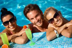 Happy people on holiday. Happy young people on holiday, smiling in swimming pool Royalty Free Stock Photos