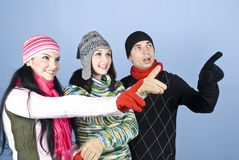 Happy people indicate up with fingers. Happy three people friends in winter clothes indicate up with fingers and smiling and looking surprised,check also my Stock Photos