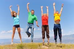 Happy people  jump. Family of four jump up in the mountains Royalty Free Stock Images