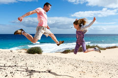 Happy people jumping on a beach. A girl and her father enjoying their vacations Royalty Free Stock Image